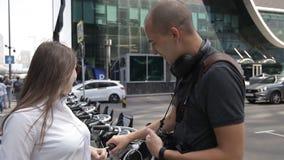 Os turistas, um homem e uma mulher, comunicam perto do planeamento alugado da bicicleta uma excursão da cidade video estoque