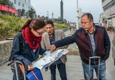 Os turistas veem o mapa para o curso do verão imagem de stock royalty free