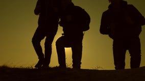 os turistas viajam com trouxas Trabalhos de equipa dos executivos Movimento lento os viajantes escalam o monte nos raios do filme