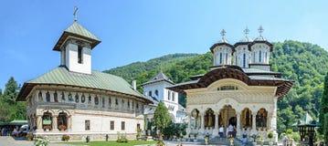 Os turistas visitam o monastério velho em um dia do ` s do verão, detalhe de Lainici do pátio com pinturas exteriores foto de stock royalty free