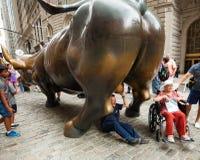 Os turistas visitam Wall Street que carrega a estátua de Bull Imagem de Stock