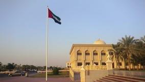 Os United Arab Emirates embandeiram a ondulação na cidade de Sharjah no por do sol