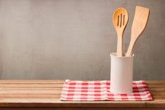 Os utensílios de madeira da cozinha na tabela com toalha de mesa sobre o grunge muram o fundo com espaço da cópia para a montagem imagem de stock royalty free