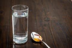 Os vários comprimidos estão em uma colher ao lado de um vidro da água em uma tabela marrom foto de stock royalty free