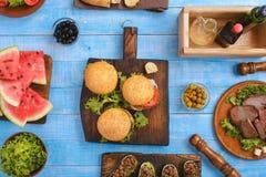 Os vários hamburgueres, bifes, encheram o abobrinha e as fatias de watermel fotografia de stock