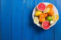 Os vários tipos de citrinos em um azul pintaram o fundo de madeira Foto de Stock