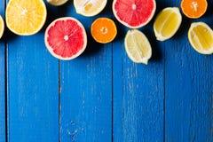 Os vários tipos de citrinos em um azul pintaram o fundo de madeira Fotografia de Stock