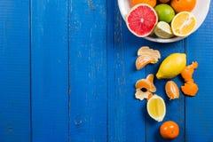Os vários tipos de citrinos em um azul pintaram o fundo de madeira Imagem de Stock