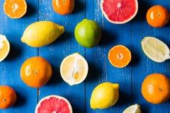 Os vários tipos de citrinos em um azul pintaram o fundo de madeira Imagens de Stock Royalty Free