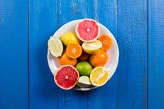 Os vários tipos de citrinos em um azul pintaram o fundo de madeira Imagem de Stock Royalty Free