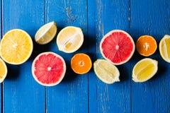 Os vários tipos de citrinos em um azul pintaram o fundo de madeira Foto de Stock Royalty Free
