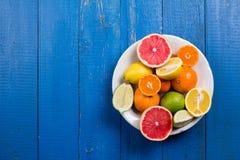Os vários tipos de citrinos em um azul pintaram o fundo de madeira Fotografia de Stock Royalty Free