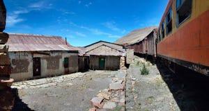 Os vagões railway abandonados com construções danificadas do armazém, Peru Foto de Stock