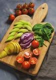 Os vegetais do vegetariano são cortados em uma placa de corte, em tomates de cereja, em espinafres, em couve, em pera, e em coent Imagens de Stock Royalty Free