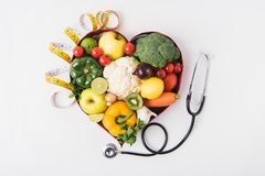 os vegetais e os frutos que colocam no coração dado forma tornam côncavos perto do estetoscópio e da fita de medição fotos de stock