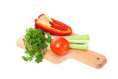 Os vegetais (pimenta, tomate, salsa) encontram-se na placa de corte Foto de Stock