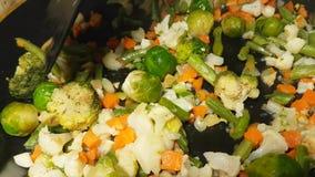Os vegetais são fritados em uma bandeja dos brócolis filme