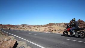 Os velomotor que conduzem na estrada/estrada vazias no deserto ajardinam video estoque