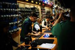 Os vendedores forem atrás do contador, um vendedor estão datilografando algo no teclado, quando loja dos povos na loja video da f imagem de stock