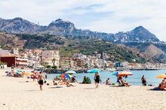 Os veraneantes na areia encalham na cidade de Giardini Naxos Imagens de Stock Royalty Free