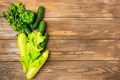Os verdes verdes frescos do pepino do abobrinha dos vegetais salpicam o fundo de madeira Vegetarianismo saud?vel do alimento Quad imagens de stock royalty free