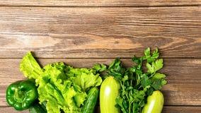 Os verdes verdes frescos do pepino do abobrinha dos vegetais salpicam o fundo de madeira Vegetarianismo saud?vel do alimento Quad fotografia de stock