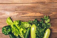 Os verdes verdes frescos do pepino do abobrinha dos vegetais salpicam o fundo de madeira Vegetarianismo saud?vel do alimento Quad imagem de stock royalty free