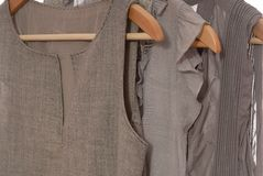 Os vestidos cinzentos estão em ganchos. Imagens de Stock Royalty Free