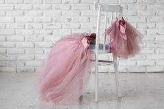 Os vestidos do ` s das crianças do verão penduram em ganchos na cadeira traseira do ` s das crianças Lugar para o texto Imagens de Stock Royalty Free