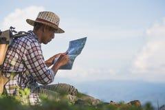 Os viajantes com trouxa verificam o mapa para encontrar sentidos em wildern imagens de stock royalty free