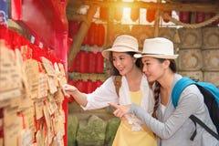 Os viajantes das amigas que olham rezam a placa Imagens de Stock Royalty Free