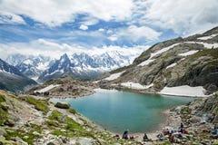 Os viajantes descansam no limiar do lago da montanha, Chamonix Fotos de Stock Royalty Free
