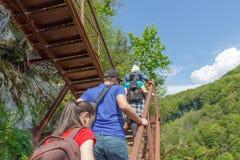 Os viajantes viajam na estrada artificial nas montanhas garganta, nuvens Trekking junto Fotografia de Stock