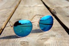 Os vidros com vidros azuis no sol encontram-se em uma viagem de madeira do resto do assoalho refletida em um vidro imagens de stock royalty free