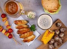Os vidros da cerveja com asas de galinha, hamburguer, bolas de carne, grelharam o milho e os vegetais Mordidas da cerveja Fotos de Stock Royalty Free