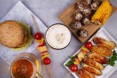 Os vidros da cerveja com asas de galinha, hamburguer, bolas de carne, grelharam o milho e os vegetais Mordidas da cerveja Foto de Stock Royalty Free
