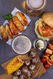 Os vidros da cerveja com asas de galinha, hamburguer, bolas de carne, grelharam o milho e os vegetais Mordidas da cerveja Imagem de Stock Royalty Free