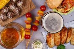 Os vidros da cerveja com asas de galinha, hamburguer, bolas de carne, grelharam o milho e os vegetais Mordidas da cerveja Imagem de Stock