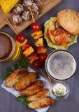 Os vidros da cerveja com asas de galinha, hamburguer, bolas de carne, grelharam o milho e os vegetais Mordidas da cerveja Fotos de Stock