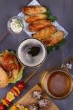 Os vidros da cerveja com asas de galinha, hamburguer, bolas de carne, grelharam o milho e os vegetais Mordidas da cerveja Fotografia de Stock Royalty Free