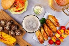 Os vidros da cerveja com asas de galinha, hamburguer, bolas de carne, grelharam o milho e os vegetais Mordidas da cerveja Fotografia de Stock