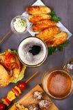 Os vidros da cerveja com asas de galinha, hamburguer, bolas de carne, grelharam o milho e os vegetais Mordidas da cerveja Imagens de Stock Royalty Free