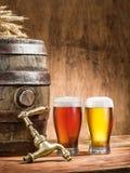 Os vidros da cerveja e da cerveja inglesa barrel na tabela de madeira Fotos de Stock