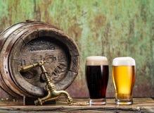 Os vidros da cerveja e da cerveja inglesa barrel na tabela de madeira Fotos de Stock Royalty Free