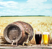 Os vidros da cerveja e da cerveja inglesa barrel na tabela de madeira Imagem de Stock