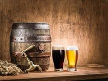 Os vidros da cerveja e da cerveja inglesa barrel na tabela de madeira Fotografia de Stock