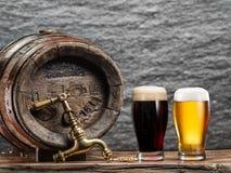 Os vidros da cerveja e da cerveja inglesa barrel na tabela de madeira Imagens de Stock