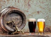 Os vidros da cerveja e da cerveja inglesa barrel na tabela de madeira Brewe do ofício Fotos de Stock