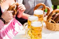 Os vidros da cerveja e do pretzel na cerveja alemão jardinam Imagens de Stock Royalty Free