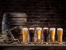 Os vidros da cerveja e da cerveja inglesa barrel na tabela de madeira Cervejaria do ofício imagens de stock